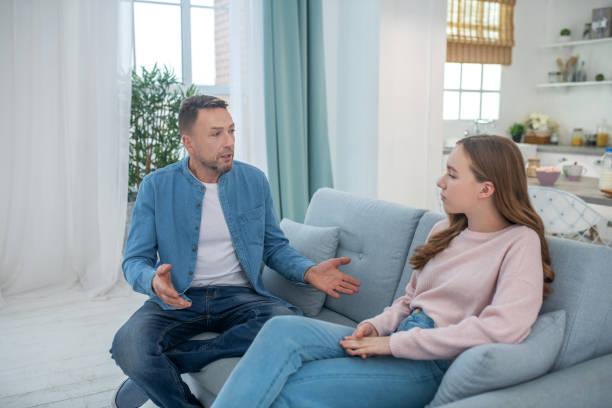 Papa im Gespräch mit trauriger Tochter, beide sitzen auf der Couch. – Foto