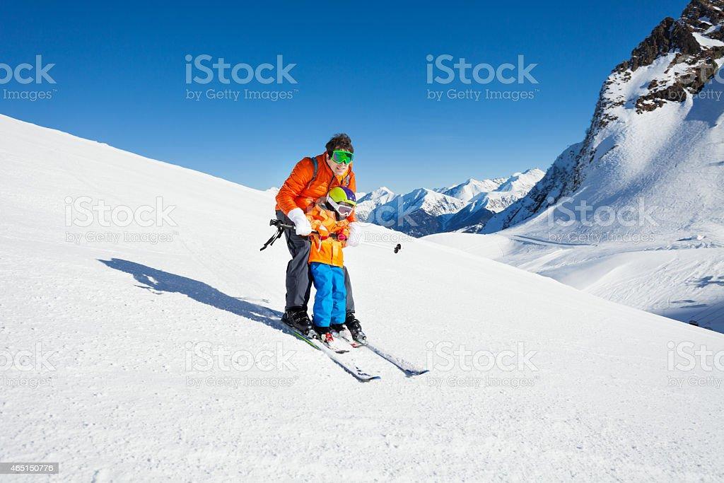 Dad teach little son to ski in mountains stock photo