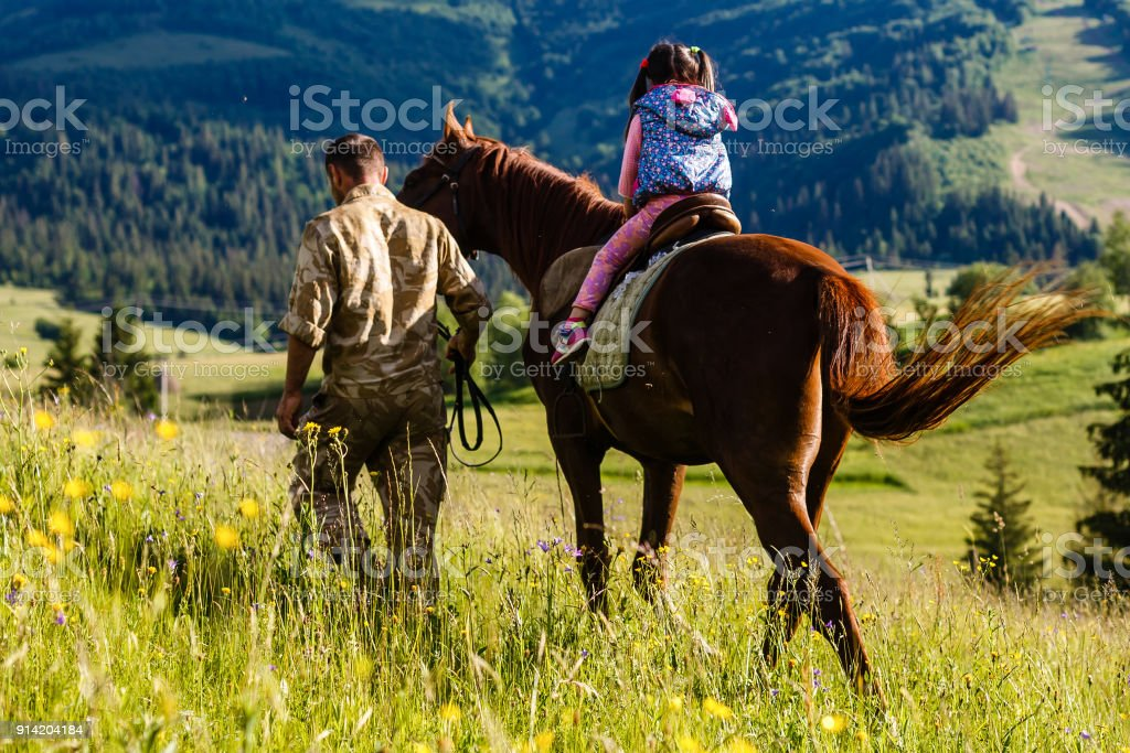 Dad teaches his daughter to ride a horse. Lesson with Riding Instructor. stock photo