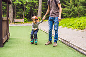 Dad teaches son to rollerblade in the park