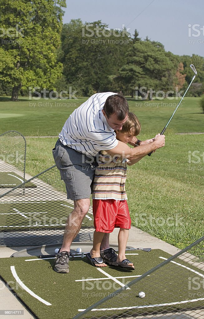 Dad Teaching Son Golf royalty-free stock photo