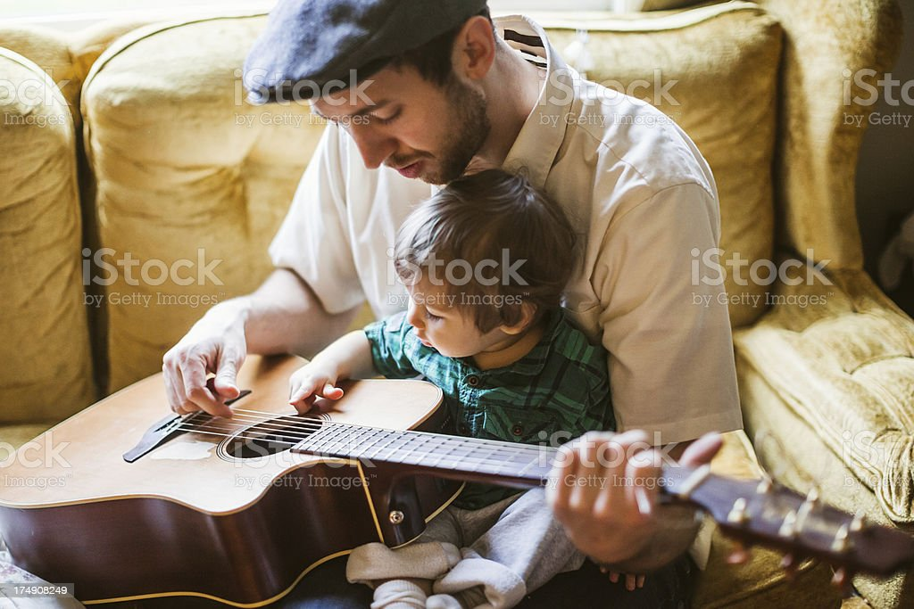 Dad Teaching Toddler to Play Instrument stock photo