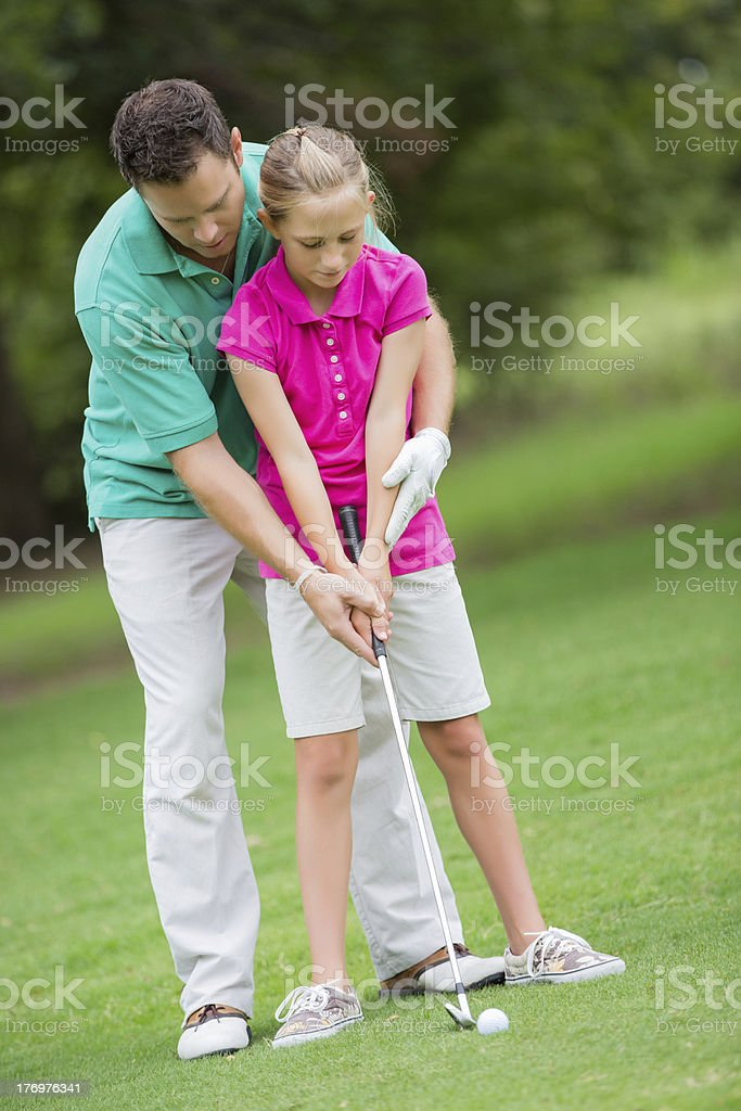 Dad teaching young daughter to play golf on course royalty-free stock photo