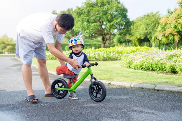 Dad tech son to ride balance bike stock photo