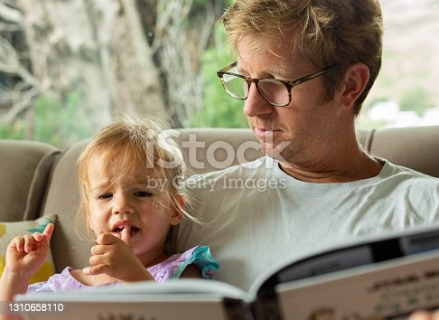 A father sitting next to his crying daughter at home, trying to be patient and understanding.