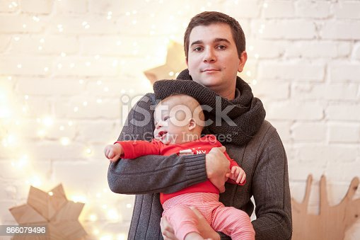 678651100 istock photo Dad wears knitted sweater and scarf holds on his hands a small son in red T-shirt standing in a bright room against a white brick wall with light bulbs garland 866079496