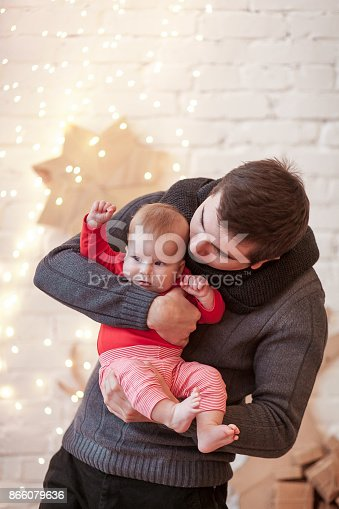 678651100 istock photo Dad wears knitted sweater and scarf holds on his hands a small son in red T-shirt standing in a bright room against a white brick wall with light bulbs garland 866079636