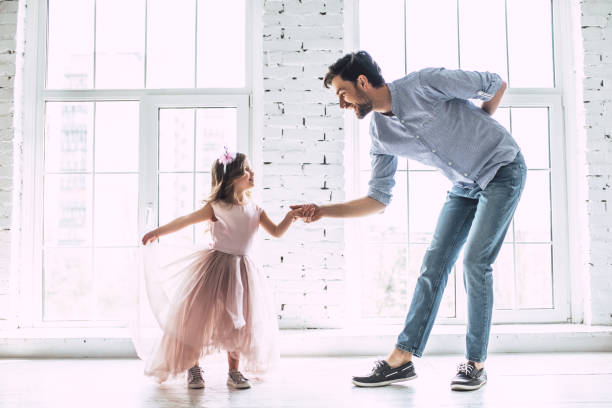 Dad with daughter at home I love you, dad! Handsome young man is dancing at home with his little cute girl. Happy Father's Day! father stock pictures, royalty-free photos & images