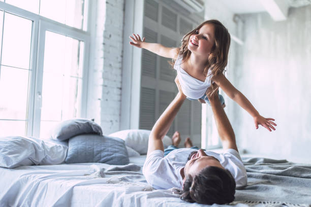 Dad with daughter at home I love you, dad! Handsome young man at home with his little cute girl are having fun together. Happy Father's Day! bed furniture stock pictures, royalty-free photos & images
