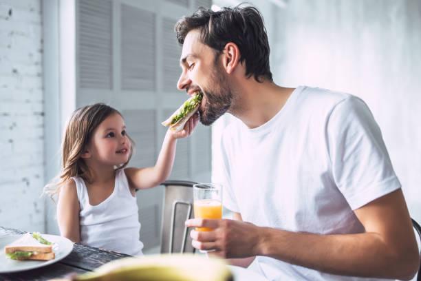 padre con hija en casa - desayuno fotografías e imágenes de stock