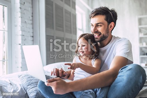 I love you, dad! Handsome young man at home with his little cute girl are lying in bed with laptop. Happy Father's Day!