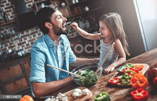 Handsome man and his little cute daughter are cooking on kitchen. Making salad. Healthy lifestyle concept.