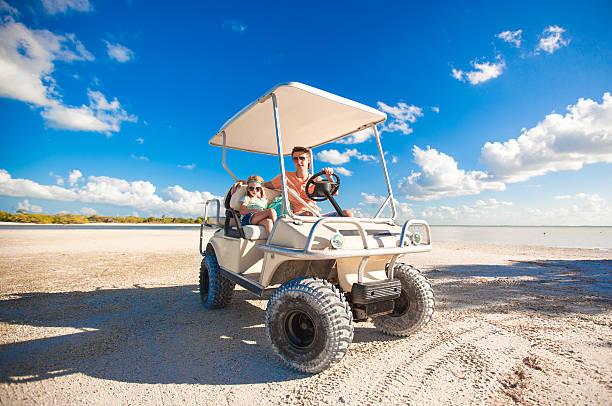 Père de ses filles conduire une voiturette de golf au plage tropicale - Photo