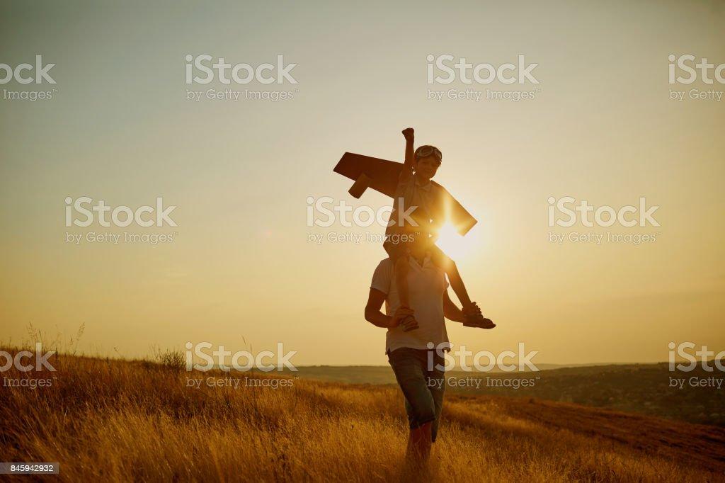 Papa avec son fils en costume du pilote au coucher du soleil dans la nature. - Photo