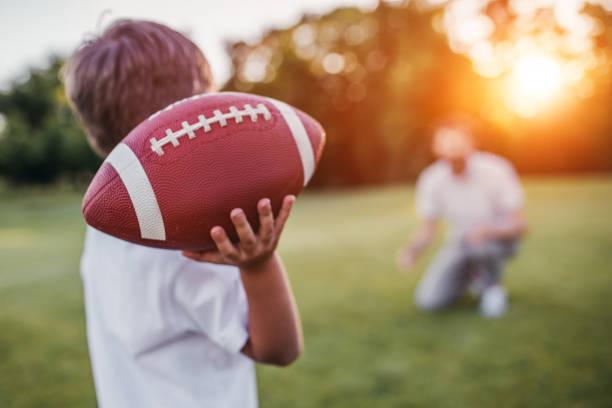 Vater mit Sohn spielt American football – Foto