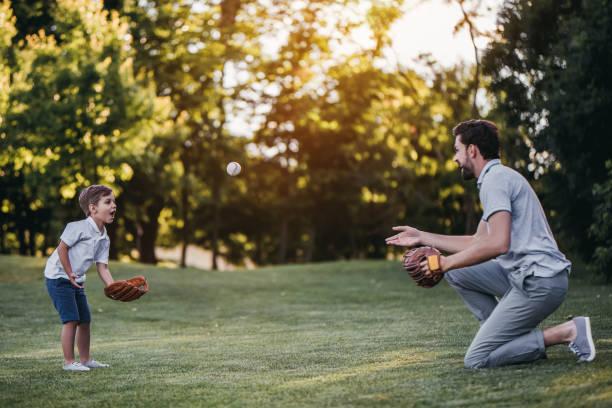 dad with son playing baseball - afferrare foto e immagini stock