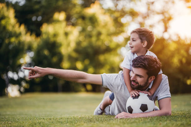 Dad with son playing football, soccer stock photo