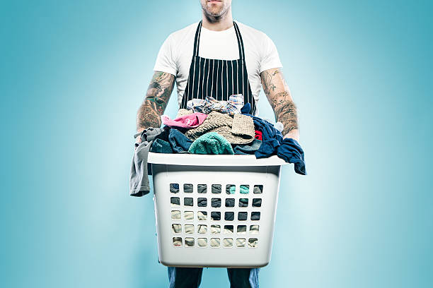 Dad with Tattoos Does Laundry A man with tattoo sleeves on both of his arms wears an apron and holds a full laundry basket of dirty clothes ready to be washed.  Could be single guy, father, husband; whatever the case, he's not afraid to help out with domestic chores around the home.  Blue studio background.  Horizontal with copy space. laundry basket stock pictures, royalty-free photos & images