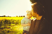 2 year old little girl with her daddy in field on sunny spring day, strong lighting.