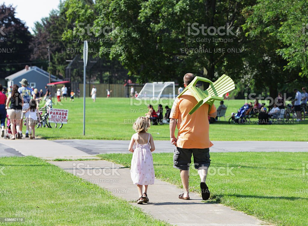 Daddy Carrying Daughter's July 4th Parade Chair stock photo