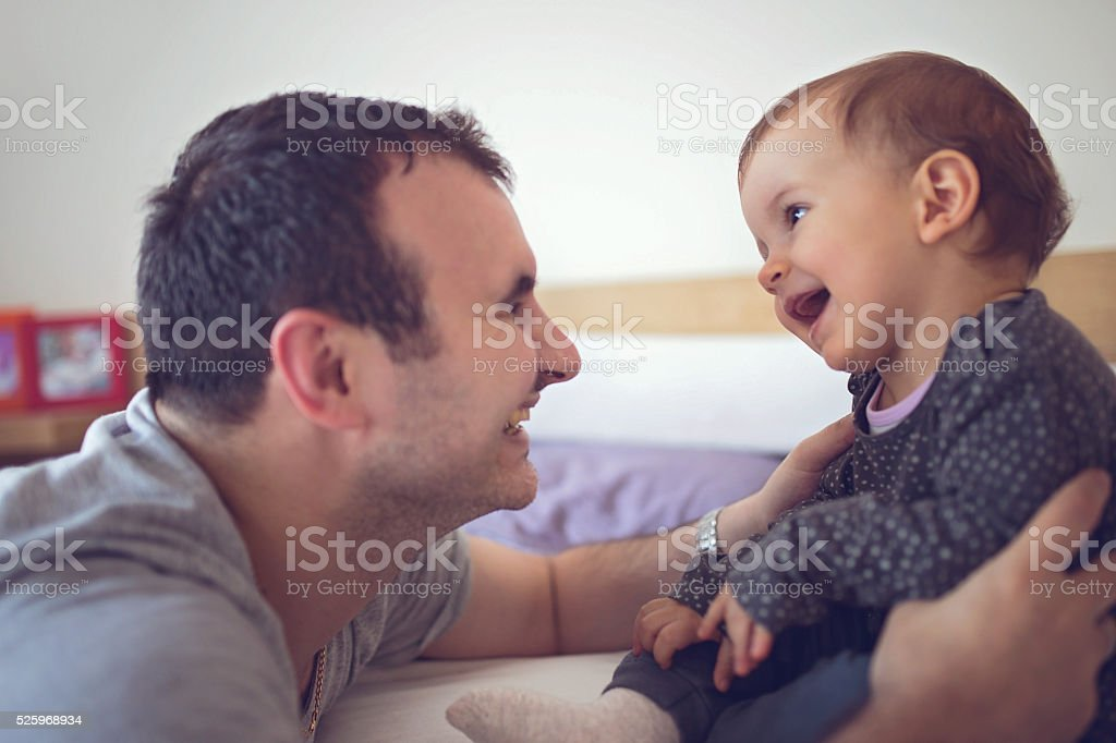 Daddy entertains baby stock photo