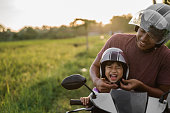daddy help her daughter to fasten the helmet while riding a motorcycle scooter
