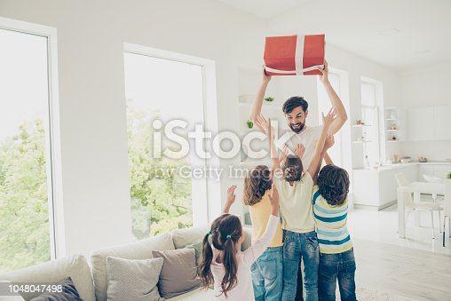 istock Daddy hold prize above head, four children up from cozy, comfort couch in modern light interior apartment and try to reach the gift. Babysitter christmas xmas 1048047498