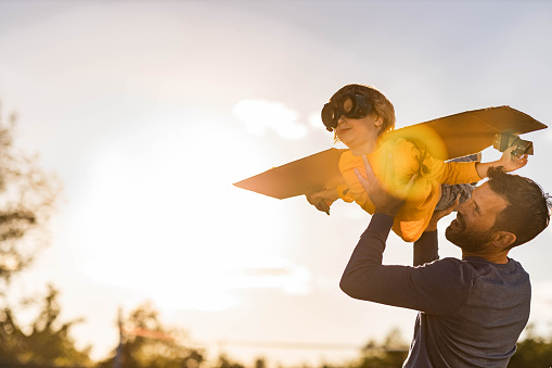 Happy single father having fun with his small boy who is pretending to be an airplane in nature. Copy space.
