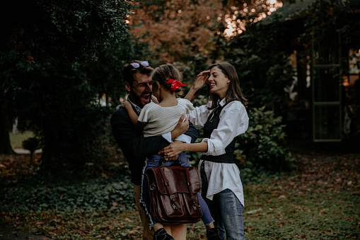 Young caucasian modern family with one child having quality time together in a city park. Young father just came back from the work.