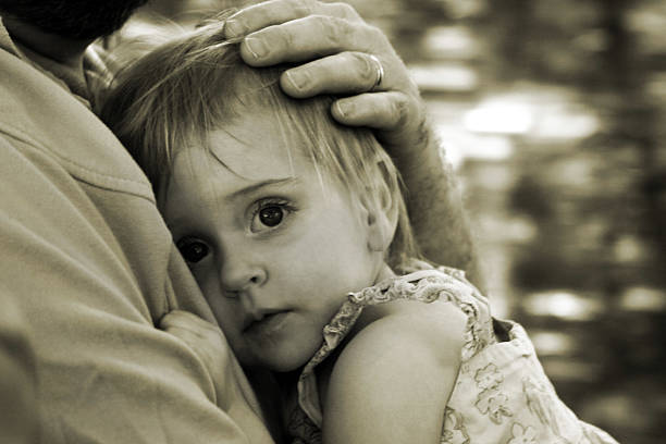 Daddy Protect Me: Girl Clinging to Father stock photo