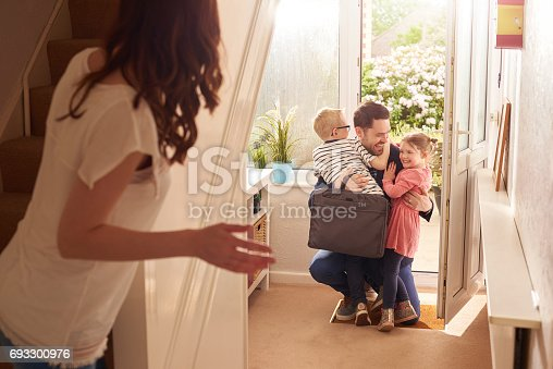 a young family rush to the front door as daddy comes home from work or a stint away .