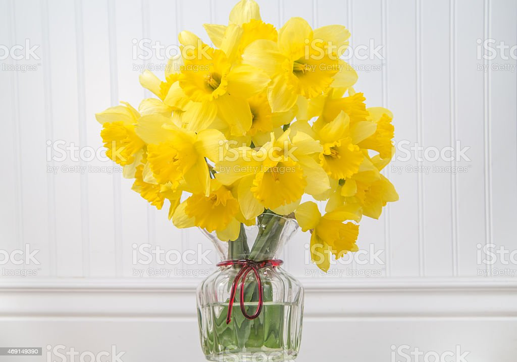 Daffodils in a vase in rustic setting - horizontal stock photo