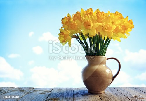 istock Daffodils in vase on wooden table 646011030