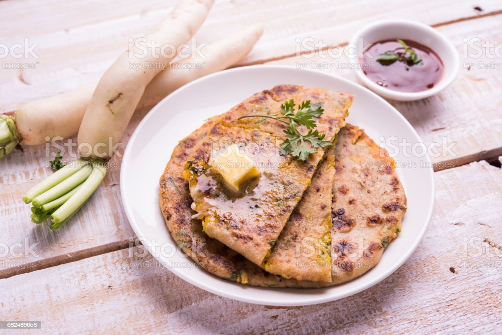 Daikon, radish, mooli or muli paratha or stuffed radish paratha, indian or pakistani favourite recipe served with butter and tomato ketchup, selective focus royalty-free stock photo