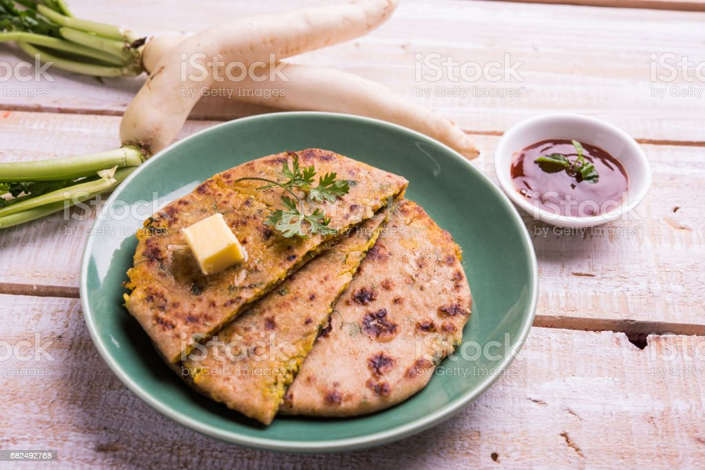Daikon, radish, mooli or muli paratha or stuffed radish paratha, indian or pakistani favourite recipe served with butter and tomato ketchup, selective focus Стоковые фото Стоковая фотография