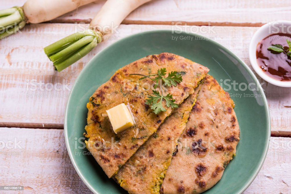 Daikon, radish, mooli or muli paratha or stuffed radish paratha, indian or pakistani favourite recipe served with butter and tomato ketchup, selective focus stock photo