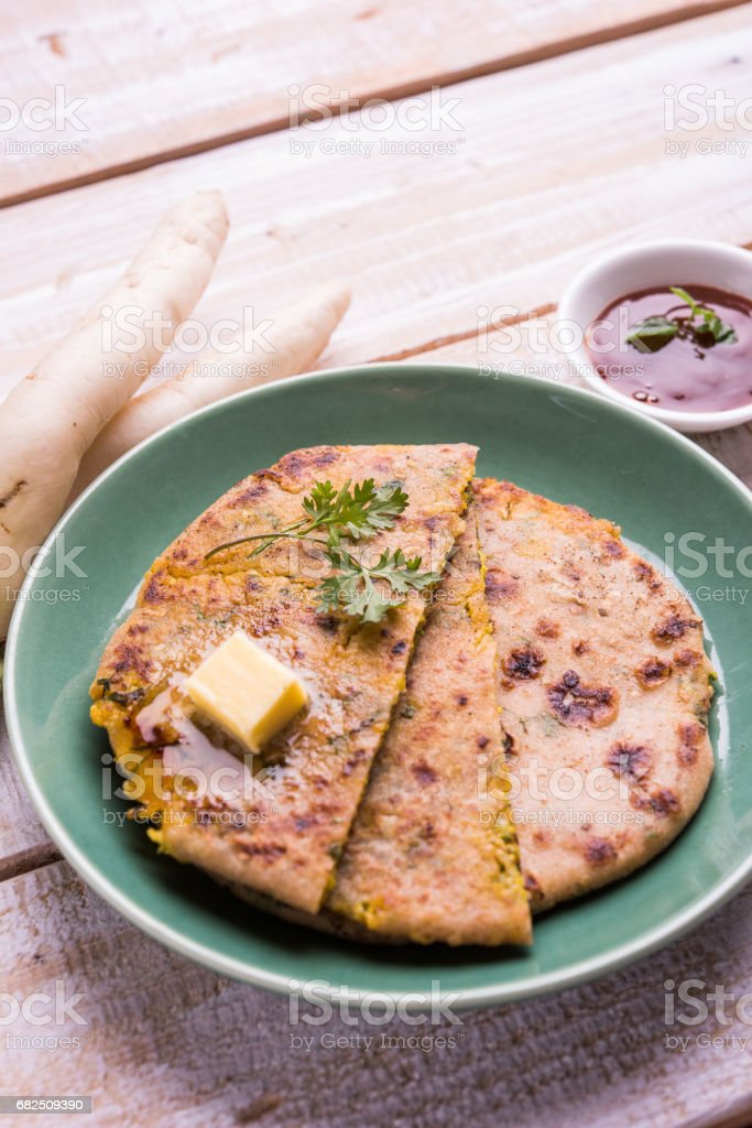 Daikon, radish, mooli or muli paratha or stuffed radish paratha, indian or pakistani favourite recipe served with butter and tomato ketchup, selective focus royalty-free stock photo