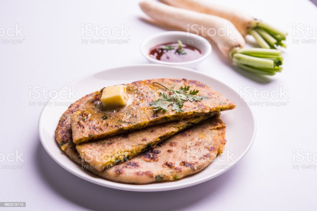 Daikon, radish, mooli or muli paratha or stuffed radish paratha, indian or pakistani favourite recipe served with butter and tomato ketchup, selective focus foto de stock royalty-free