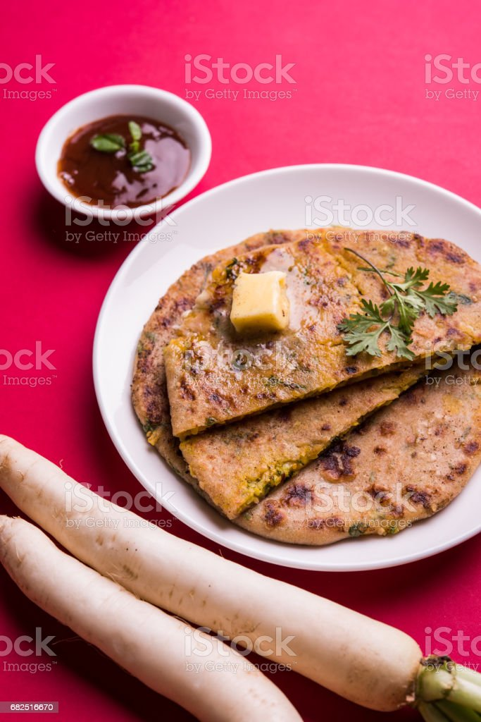 Daikon, radish, mooli or muli paratha or stuffed radish paratha, indian or pakistani favourite recipe served with butter and tomato ketchup, selective focus Стоковые фото Стоковая фотография