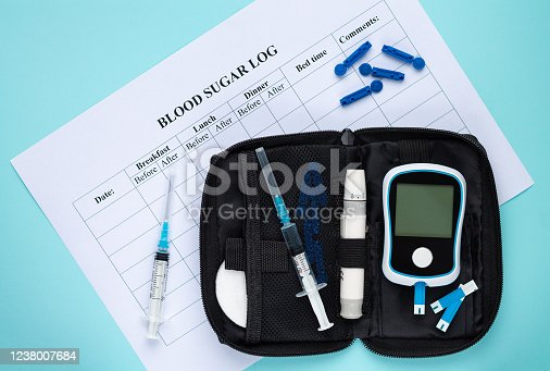 istock Daily blood glucose log with sugar or insulin checking measurement set on light blue background top view 1238007684
