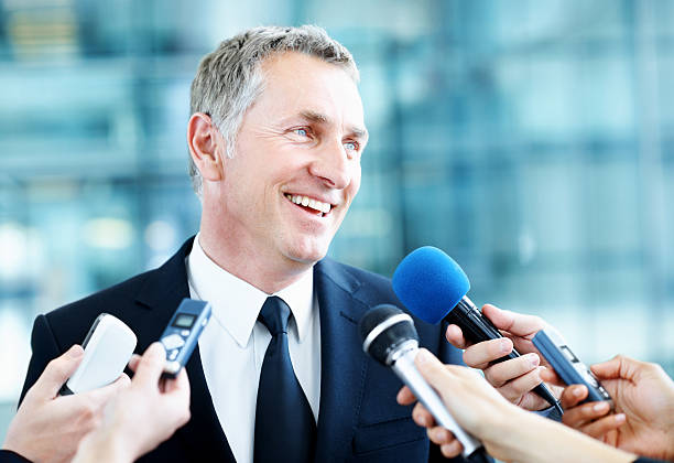 Daily business for a enterprise leader Happy mature senator standing at a press conference with various microphones held in front of him spokesperson stock pictures, royalty-free photos & images