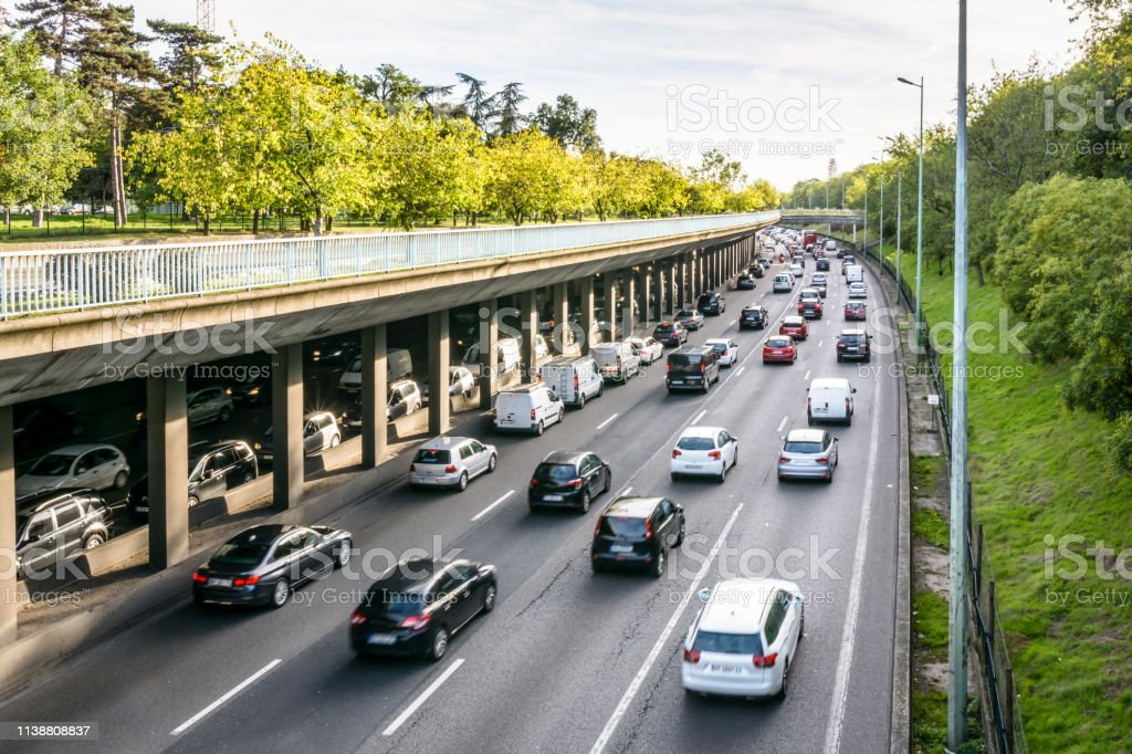 Daily heavy traffic on the ring road of Paris at the evening rush hour. Daily heavy traffic on the half-covered western part of the eight lanes ring road of Paris, known as the boulevard peripherique, at the evening rush hour. Air Pollution Stock Photo