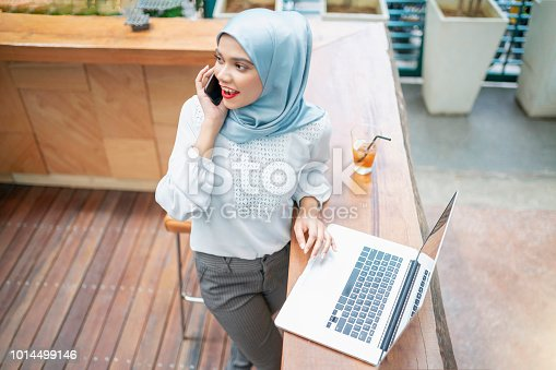 Beautiful malaysian businesswoman talking on the phone while at work.