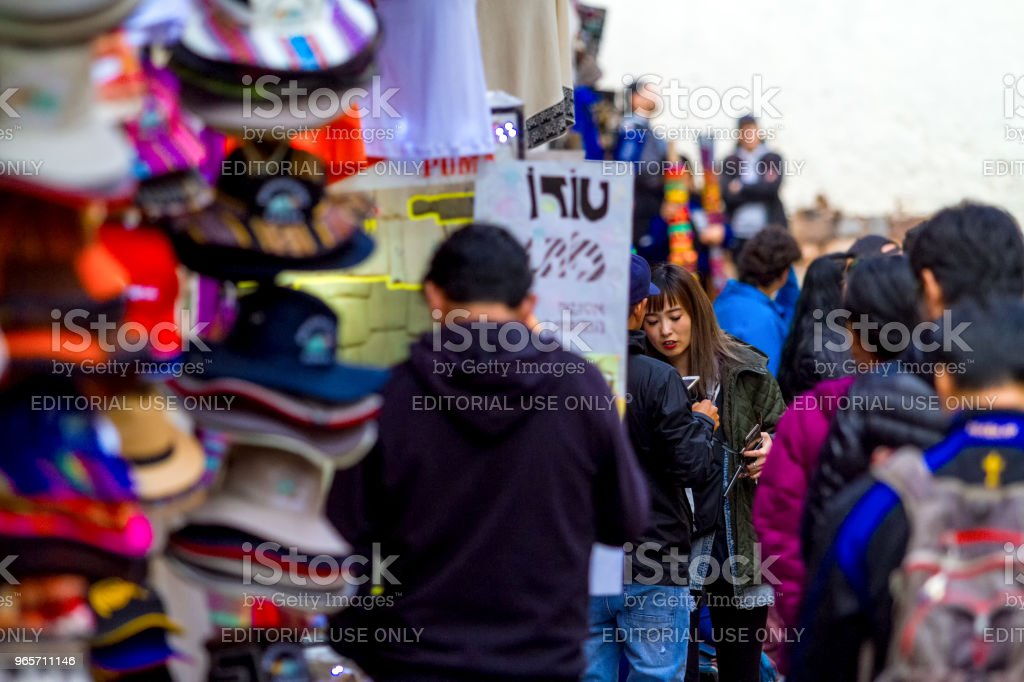 Daily Image. A Korean woman consults for souvenirs at a post in the historic center of Cusco - Royalty-free Adult Stock Photo