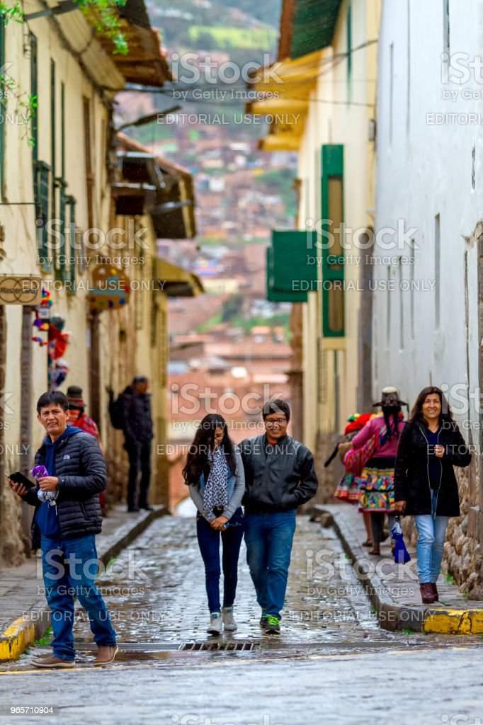Daily Image. After the rain, young couple of tourists walks through the streets of the San Blas neighborhood of Cusco - Royalty-free Alley Stock Photo