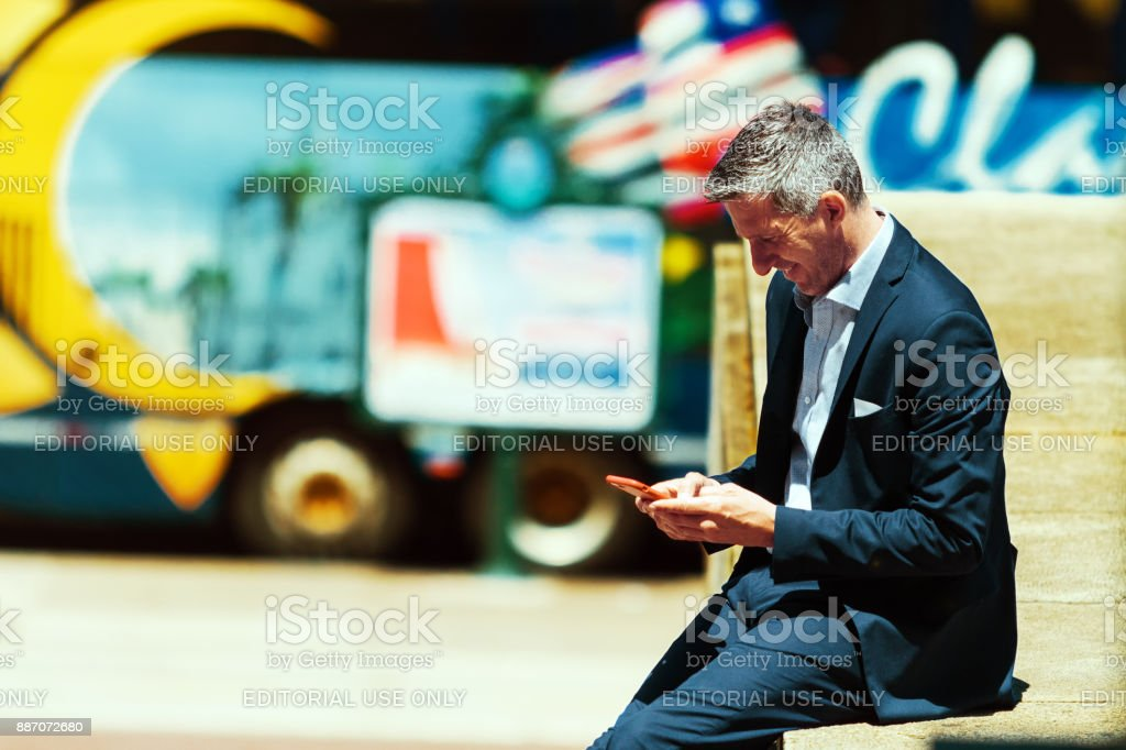 Daily image of a gray-haired man with suit chating through his smartphone on the street under the midday sun stock photo