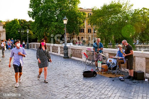 Rome, Italy, May 22 -- Some street artists play on the ancient Ponte Sisto near Trastevere, while people walk protected by a medical mask during the slow reopening towards a normal life after two months lockdown due to Covid-19.