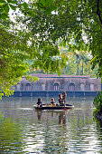 Kumarakom, Kerala/India - September 23, 2013: A woman with her three young kids, on a bamboo raft, passing through the narrow canal - going about their daily activities in the backwaters of Kerala. A tourist houseboat can be seen in the background.