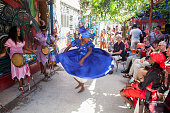 A dancer in a folk costume dances to the rhythm of traditional music surrounded by tourists in the Callejón de Hamel, one of the most visited places in Havana