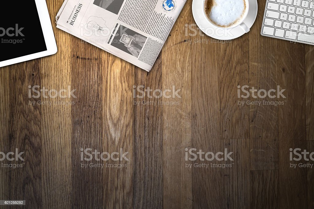 Daily newspaper and tablet pc on the wooden table. - Photo